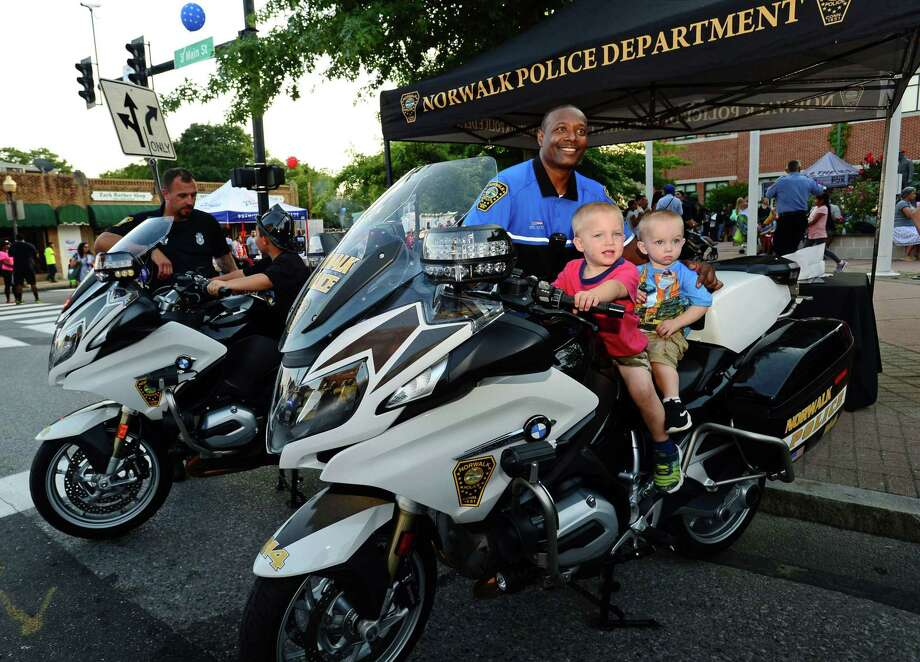 Officer Max Sixto poses with Daniel and Isaiah Zazula, 2 and 1, as they sit on one of the department's motorcycles during the Norwalk Police Department National Night Out at police headquarters on Monroe Street on Tuesday. National Night Out is a community-building campaign to promote police-community partnerships and neighborhood camaraderie. Local businesses gave away samples and goodies, and restaurants handed out bites to eat as well as hands-on demonstrations by first responders, and other activities for kids. Photo: Erik Trautmann / Hearst Connecticut Media / Norwalk Hour