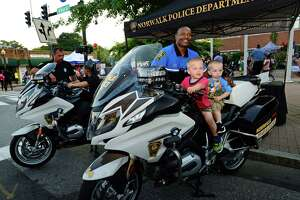 Officer Max Sixto poses with Daniel and Isaiah Zazula, 2 and 1, as they sit on one of the department's motorcycles during the Norwalk Police Department National Night Out at police headquarters on Monroe Street on Tuesday. National Night Out is a community-building campaign to promote police-community partnerships and neighborhood camaraderie. Local businesses gave away samples and goodies, and restaurants handed out bites to eat as well as hands-on demonstrations by first responders, and other activities for kids.