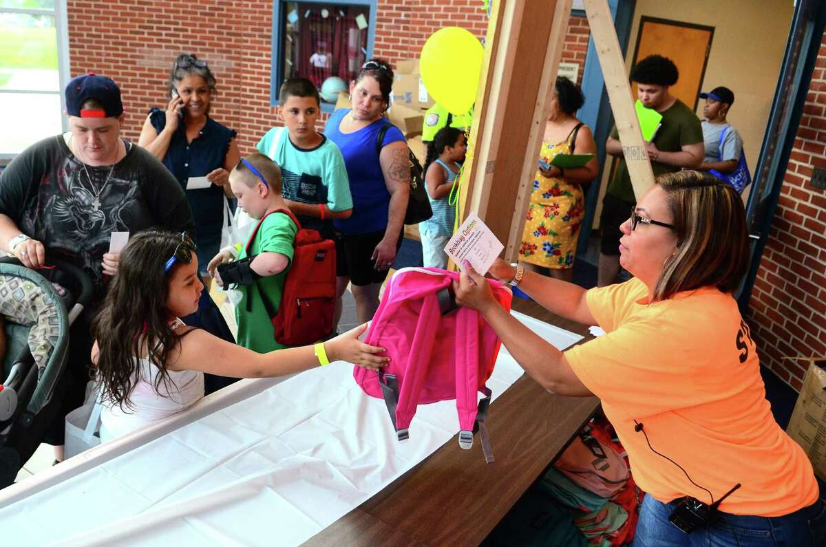Nevaeh Taylor, 6, gets a new book bag from Jasmime Ruiz during the Elm City Communities/Housing Authority of New Haven's annual Back to School Fair at Clinton Avenue School in New Haven Tuesday. In addition to activities for the kids such as face painting and snacks, families were able to access resources for education and health services.