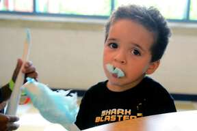 """Ray Morales, 2, enjoys cotton candy during the Elm City Communities/Housing Authority of New Haven's annual """"Back to School Fair"""" at Clinton School in New Haven, Conn., on Tuesday August 6, 2019. In addition to new school supplies and activities for the kids like face painting and snacks, families were able to access resources for education and health services."""