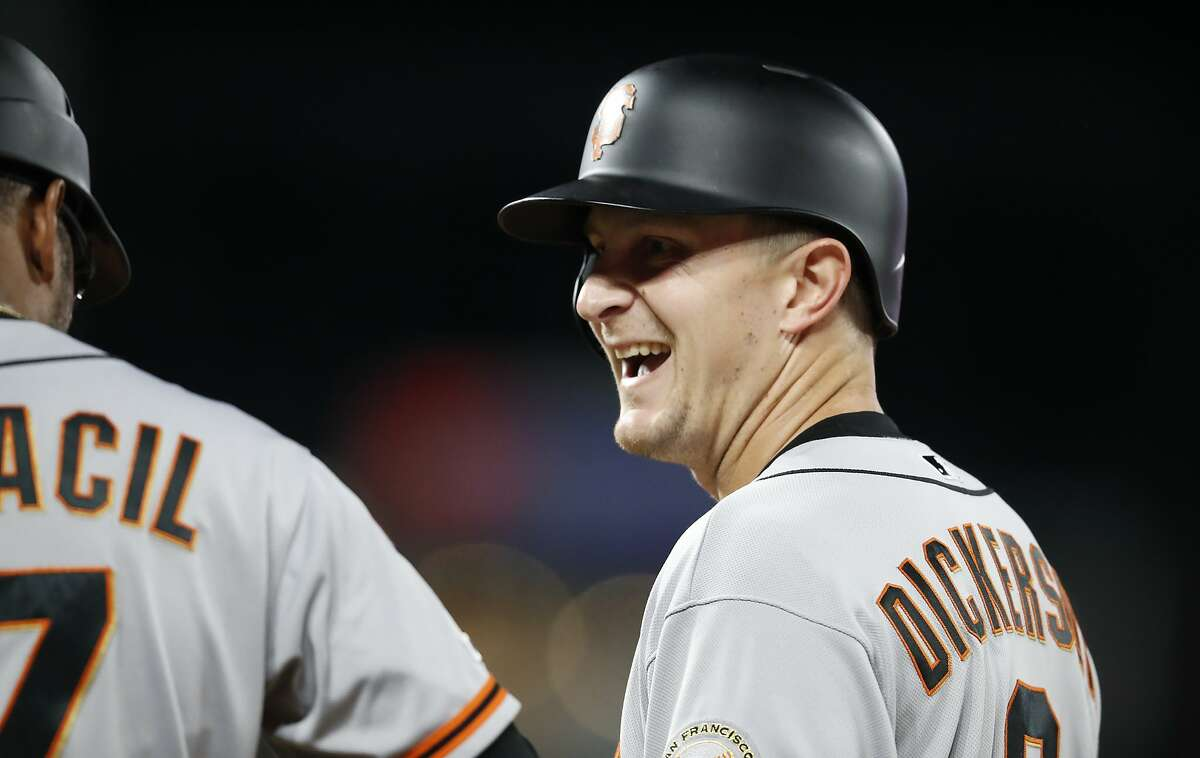 San Francisco Giants' Alex Dickerson, right, jokes with first base coach Jose Alguacil after driving in the go-ahead run with a single off Colorado Rockies relief pitcher Wade Davis during the 10th inning of a baseball game Tuesday, July 16, 2019, in Denver. The Giants won 8-4 in 10 innings. (AP Photo/David Zalubowski)