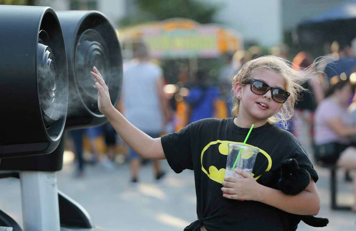 Mikayla Mojica, 9, cools off from the heat in front of misting fans as the San Antonio River Authority, Bat Conservation International, Texas Parks and Wildlife Department and San Antonio River Foundation serve as hosts for the 7th Annual Bat Loco Bash on Tuesday, Aug. 6, 2019. The free, family-friendly event took place near the Camden St. bridge on the Museum Reach segment of the San Antonio River Walk. The event featured a bat parade, educational booths, food trucks, live music and bat friends. (Kin Man Hui/San Antonio Express-News)