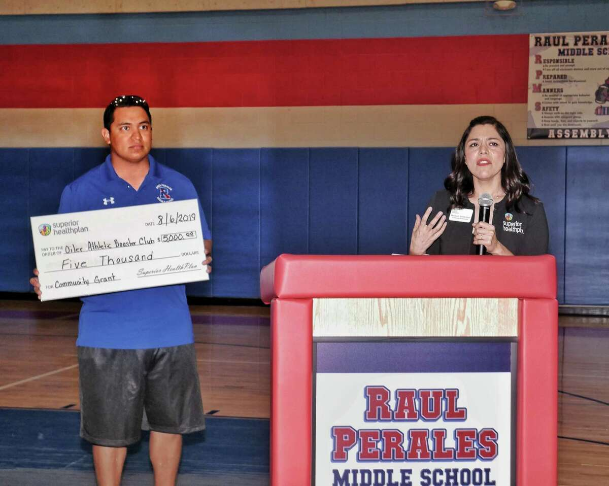 Raul Perales Middle School Campus Athletic Coordinator Jaime Saldaña is presented with a $5,000 grant for the school by Monica Santa Cruz of Superior Health Plans on Tuesday.