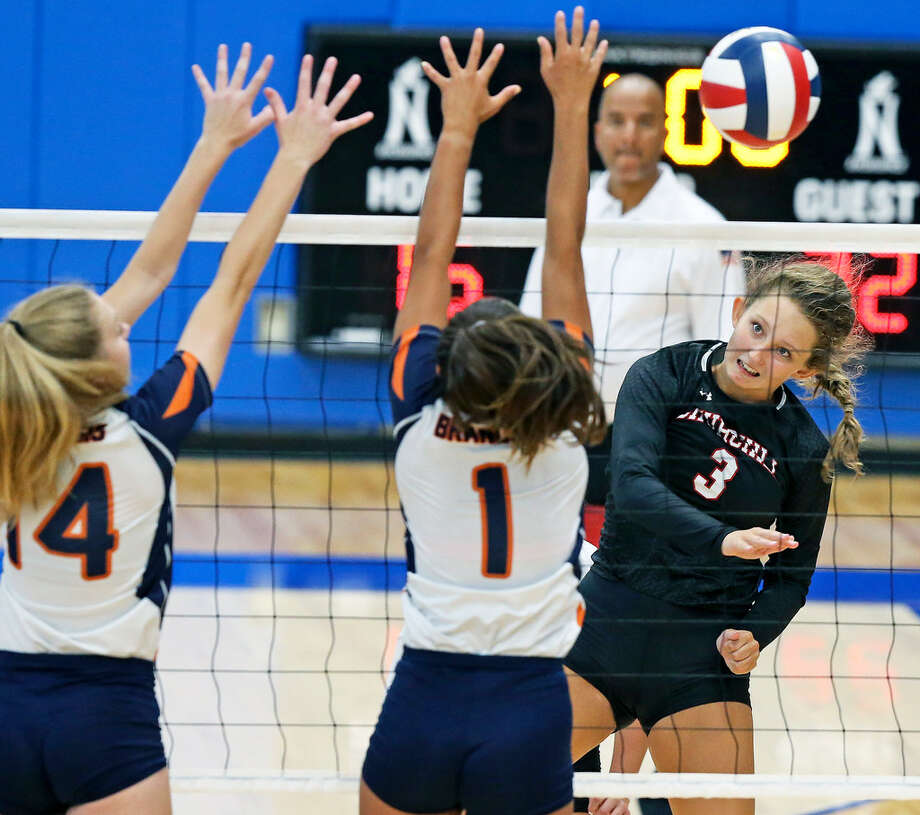 Churchill's Shayla Garrison hits around the block of two Brandeis defenders. Photo: Tom Reel