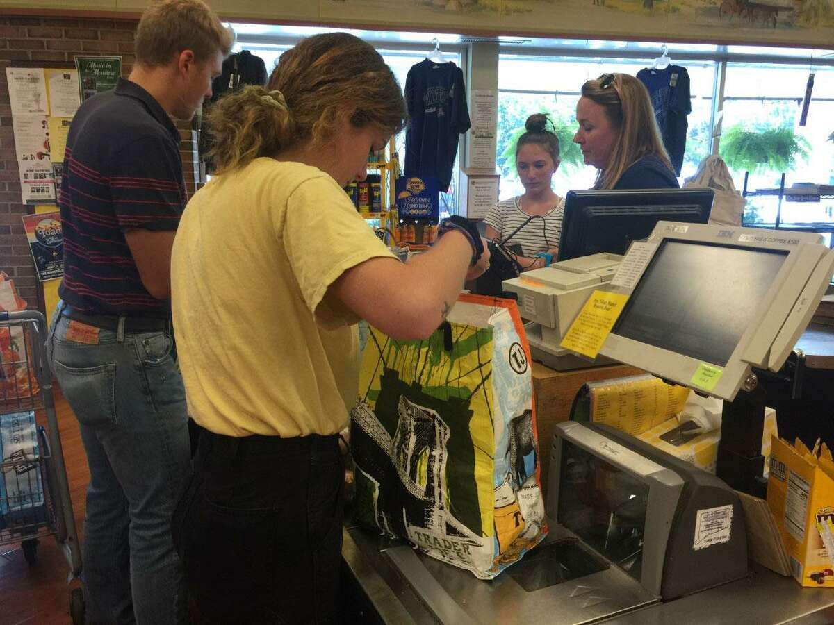 Cashiers at Village Market in Wilton work with reusable bags.