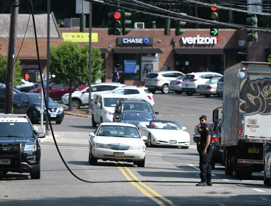 Police direct traffic safely over downed powerlines near the Glen Ridge Shopping Plaza in the Glenville section of Greenwich, Conn. the morning of Wednesday, Aug. 7, 2019. Traffic was backed up through Glenville all the way to King Street as well as the Merritt and Hutchinson River Parkways. Photo: Tyler Sizemore / Hearst Connecticut Media / Greenwich Time