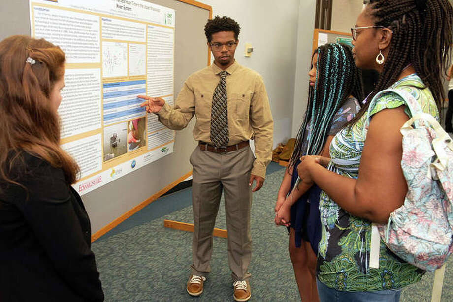 REU participant Anthony DeFreece, a sophomore studying anthropology at the University of North Texas, explains his research project to his sister, Sophia, and mother, Valerie, as his research partner, Caille Paulsen, looks on. Photo: Courtesy Of SIUE