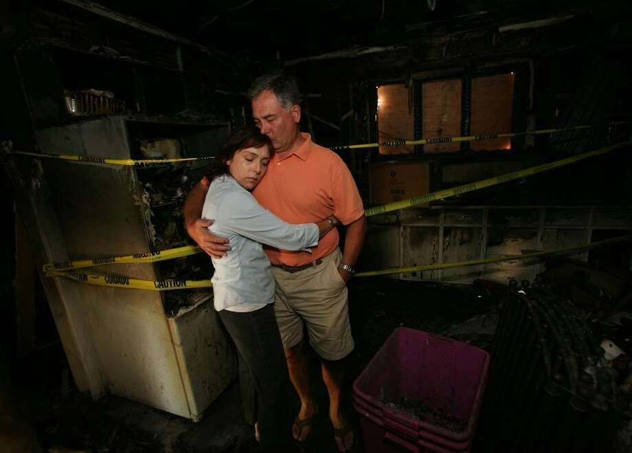 Anna and Eric Pelletier share a hug in the kitchen of their home at 46 Senior Place in Fairfield. The house was destroyed in a fire on Friday in which their two dogs perished. Photo: Brian A. Pounds / Connecticut Post