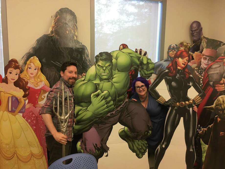 John Casiello and Kristina Lareau take a minute out of their busy days at the Ridgefield Library to take a picture next to a cardboard cutout of The Hulk. Casiello is the library's adult collection specialist and Lareau is the head of children's services. The duo have been busy organizing the fifth annual RidgeCon event Aug. 9 and Aug. 10 at the library. The library's 50 or so pop culture cutouts range from Yoda to Harry Potter to Disney princesses to the cast of The Walking Dead to Dr. Who. Photo: Stephen Coulter / Hearst