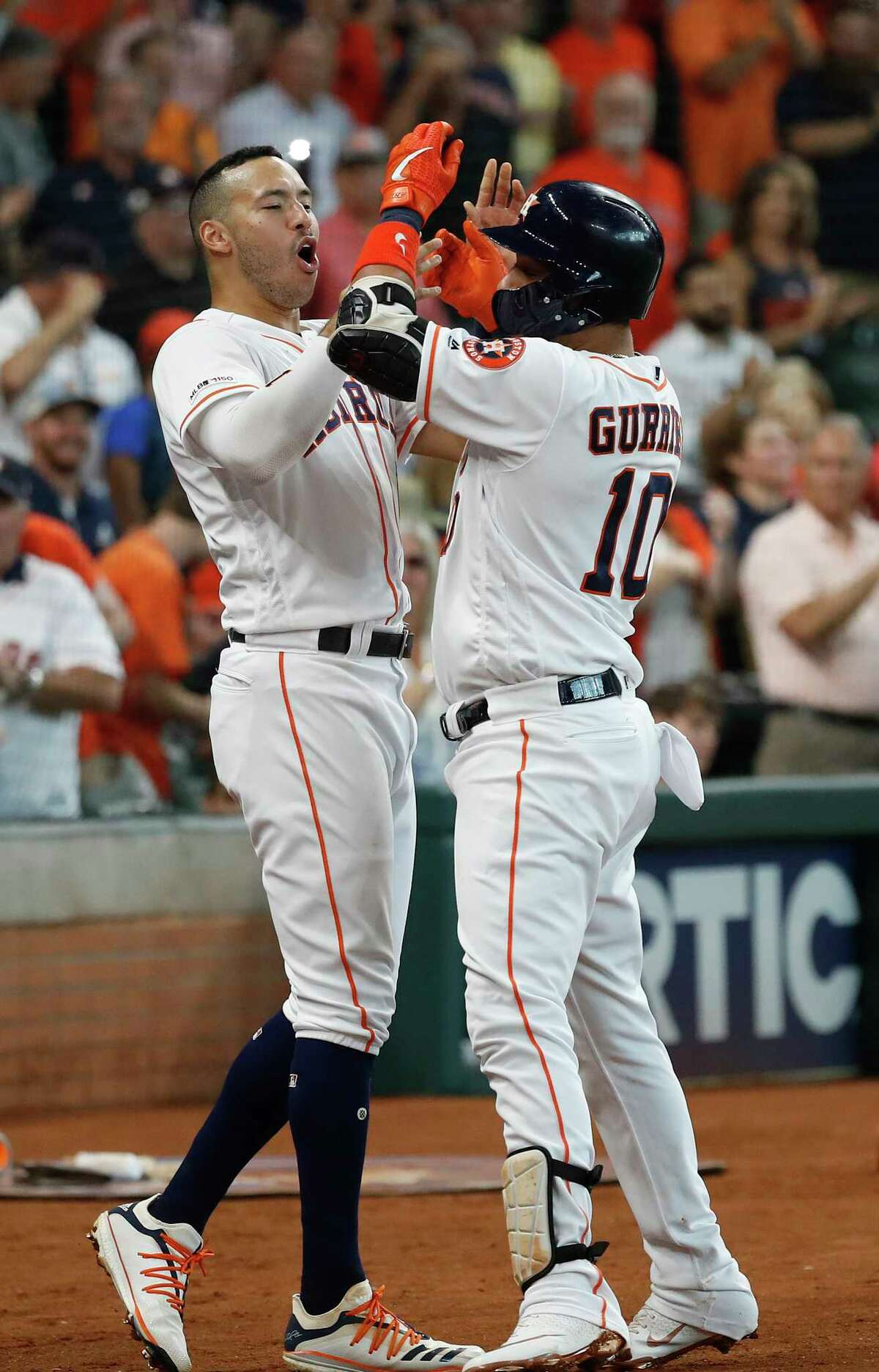 Houston Astros Yuli Gurriel (10) celebrates with Carlos Correa after hitting a three-run home run off of Colorado Rockies starting pitcher Peter Lambert during the first inning of an MLB baseball game at Minute Maid Park, Wednesday, August 7, 2019.