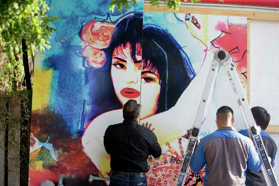 In this Tuesday, July 30, 2019 photo, from left, Ray Hernandez, David Dominguez and Alex Rodriguez, with Iconic Signs Group, install a new Selena mural on the exterior of the Food Store in the Molina neighborhood of Corpus Christi, Texas. The previous mural was painted by West Oso High School students in 1995 as a neighborhood tribute to Selena Quintanilla-Perez. (Rachel Denny Clow/Corpus Christi Caller-Times via AP) Photo: Rachel Denny Clow / Associated Press / Corpus Christi Caller-Times