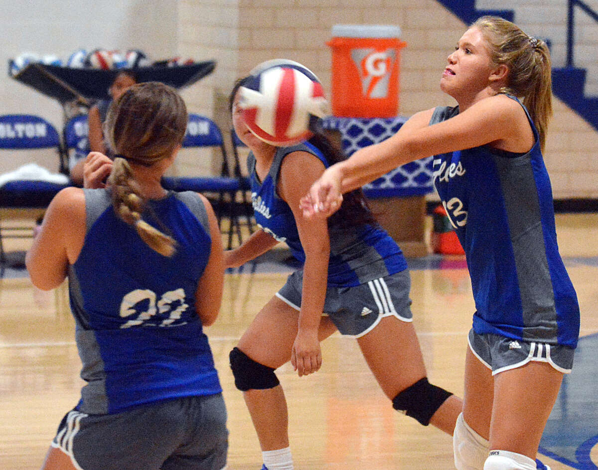 Olton's Emily Catlett comes up with the dig as teammates Shaylee Leathers (22) and Lisette Guerrero look on during their season-opening match against Loop on Tuesday at Olton Memorial Gymnasium.