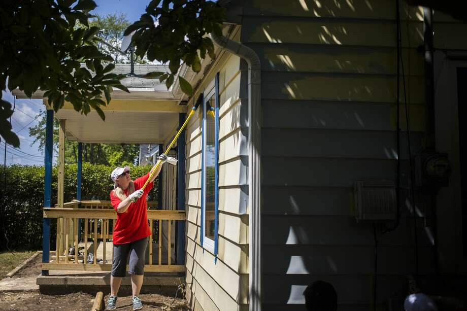 Amy Axtell clears debris from the exterior of a home while volunteering for Midland County Habitat for Humanity's Neighborhood Revitalization Initiative on Wednesday, Aug. 7, 2019. (Katy Kildee/kkildee@mdn.net) Photo: (Katy Kildee/kkildee@mdn.net)