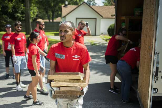 John Tsaras carries supplies while volunteering for Midland County Habitat for Humanity's Neighborhood Revitalization Initiative on Wednesday, Aug. 7, 2019. (Katy Kildee/kkildee@mdn.net)