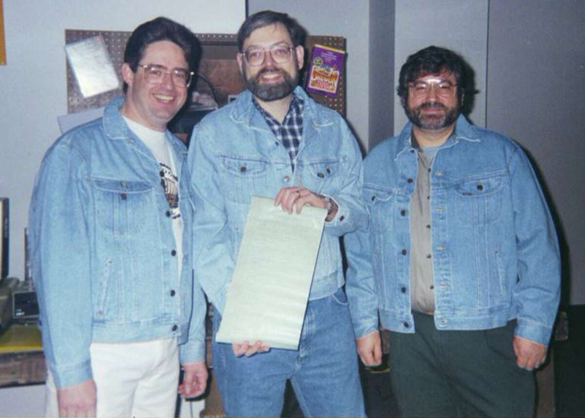 From left to right: Oregon Trail game creators Don Rawitsch, Bill Heinemann, Paul Dillenberger pose (in jean jackets, naturally) with the code for the game in 1995.
