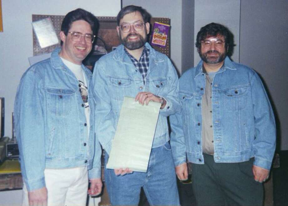 From left to right: Oregon Trail game creators Don Rawitsch, Bill Heinemann, Paul Dillenberger pose (in jean jackets, naturally) with the code for the game in 1995. Photo: Courtesy Of Don Rawitsch