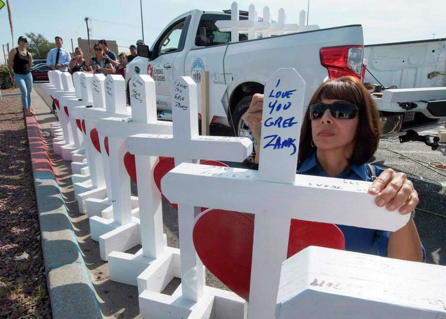 Members of the 'Crosses for Losses' group arrive at the scene with crosses for each victim, after the shooting that left 21 people dead at the Cielo Vista Mall Walmart in El Paso, Texas, on Aug. 5. Educating the public on signs of mental illness and how to help may reduce the frequency of mass shootings. Photo: MARK RALSTON /AFP /Getty Images / AFP or licensors
