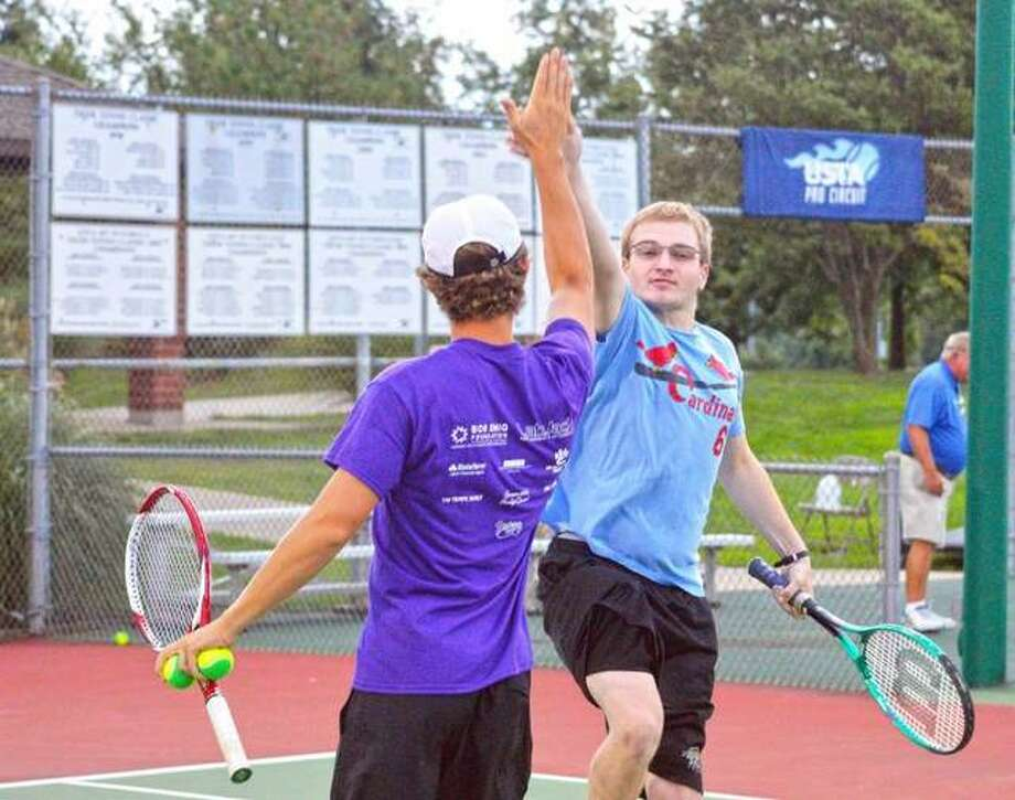 Michael Bugger, right, exchanges a high five with former Edwardsville player Jack Desse in 2017 during the sixth annual Mitch n' Friends night at the EHS Tennis Center. Mitch 'n' Friends is one of many community involvement events at the Edwardsville Futures. Photo: Scott Marion/The Intelligencer
