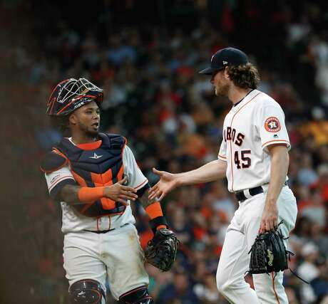 Houston Astros starting pitcher Gerrit Cole (45) shakes hands with catcher Martin Maldonado (12) after striking out Colorado Rockies Daniel Murphy to end the sixth inning of an MLB baseball game at Minute Maid Park, Wednesday, August 7, 2019.