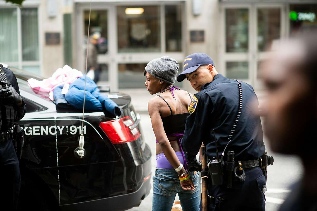 Police officers arrest a woman for an outstanding warrant in the Tenderloin on Wednesday, Aug. 7, 2019, in San Francisco.As federal authorities launched the new initiative, San Francisco police on Wednesday deployed an operation of their own in the district, arresting more than 50 people on suspicion of drug and weapons charges and warrant violations.