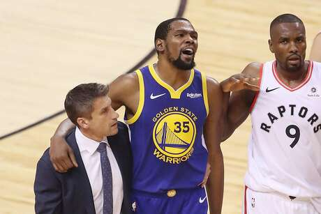Kevin Durant #35 of the Golden State Warriors is assisted off the court after sustaining an injury in the first half against the Toronto Raptors during Game Five of the 2019 NBA Finals at Scotiabank Arena on June 10, 2019 in Toronto, Canada. (Claus Andersen/Getty Images/TNS) *FOR USE WITH THIS STORY ONLY*