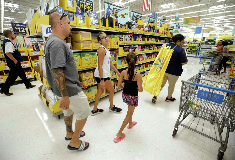 In this Tuesday, July 25, 2017 photo, Mark Spahr, left, is helped by employee Tiana Gerron, right, as he shops for school supplies with his daughters, Illeana Spahr, a sixth grader, and Elyse Spahr,  a third grader, at Walmart in Tomball, Texas. Walmart Back-to-School Helpers wearing super hero capes are stationed in the aisles to help customers. (Melissa Phillip/Houston Chronicle via AP) Photo: Melissa Phillip, MBO / Associated Press / Internal