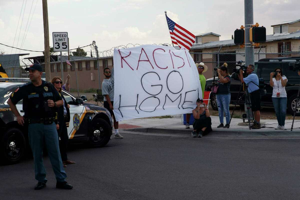 Demonstrators hold a sign as the motorcade carrying President Donald Trump arrives to visit a joint operations center to meet with first responders after the El Paso mass shooting, Wednesday, Aug. 7, 2019, in El Paso, Texas. (AP Photo/Evan Vucci)