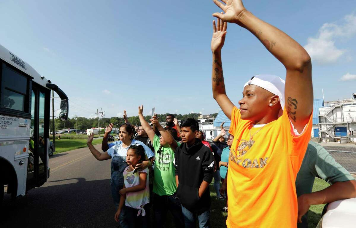 Friends, coworkers and family wave to one of several buses that are filled with detainees, following a U.S. Immigration raid at several Mississippi food processing plants, including this Koch Foods Inc., plant in Morton, Miss., Wednesday, Aug. 7, 2019. The early morning raids were part of a large-scale operation targeting owners as well as undocumented employees. (AP Photo/Rogelio V. Solis)