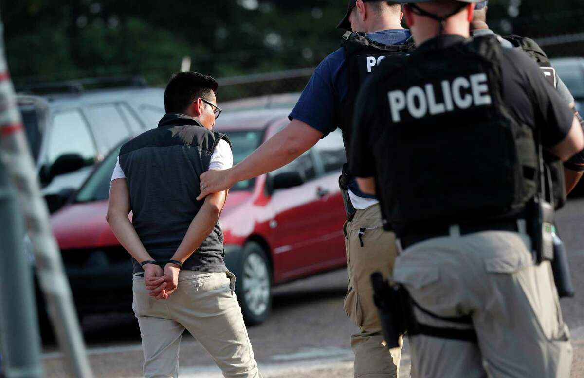 A man is taken into custody at a Koch Foods Inc. plant in Morton, Miss., on Wednesday, Aug. 7, 2019. U.S. immigration officials raided several Mississippi food processing plants on Wednesday and signaled that the early-morning strikes were part of a large-scale operation targeting owners as well as employees. (AP Photo/Rogelio V. Solis)