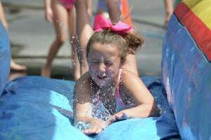 A camper enjoys a water slide as part of the Kanakuk KampOut! at the Memorial Drive Presbyterian Church on Wednesday in Houston.