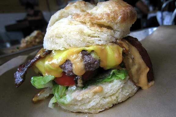 An ABC Burger comes with American cheese, poblano jam, lettuce, tomatoes and bacon on a biscuit at Alamo Biscuit Co. & Panadería.
