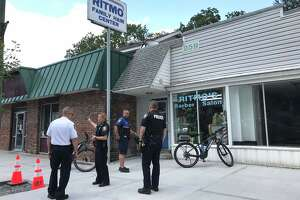 Police stand outside businesses on New Scotland Avenue Thursday as they investigate the robbery of customers at one of the establishments and a subsequent carjacking.