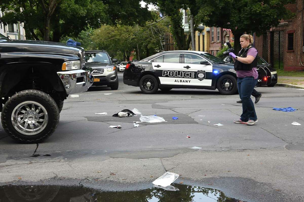 Police investigate the scene where a truck, at left, hit a pedestrian at the intersection of Madison Ave. and Dove St. on Thursday, Aug. 8, 2019 in Albany, N.Y. The man who was struck was taken away in an ambulance. (Lori Van Buren/Times Union)