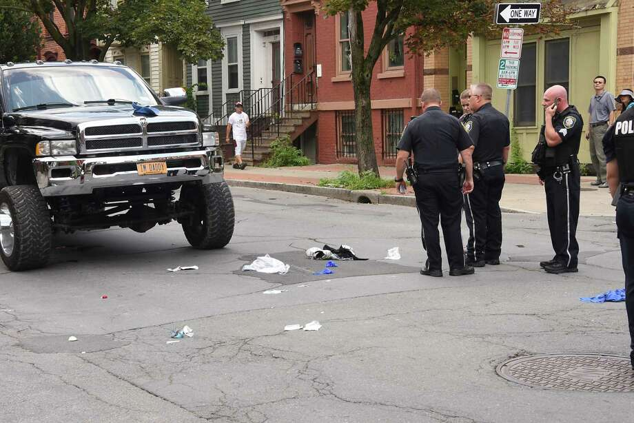Police investigate the scene where a truck, at left, hit a pedestrian at the intersection of Madison Ave. and Dove St. on Thursday, Aug. 8, 2019 in Albany, N.Y. The man who was struck was taken away in an ambulance. (Lori Van Buren/Times Union) Photo: Lori Van Buren, Albany Times Union