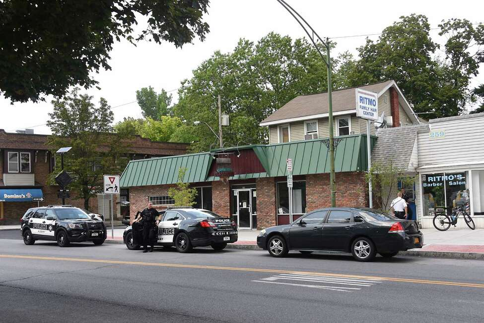 Police investigate the scene where two men armed with a gun took money from customers at Ritmo's Barber Salon, at right, at 259 New Scotland Ave. on Thursday, Aug. 8, 2019 in Albany, N.Y. (Lori Van Buren/Times Union)