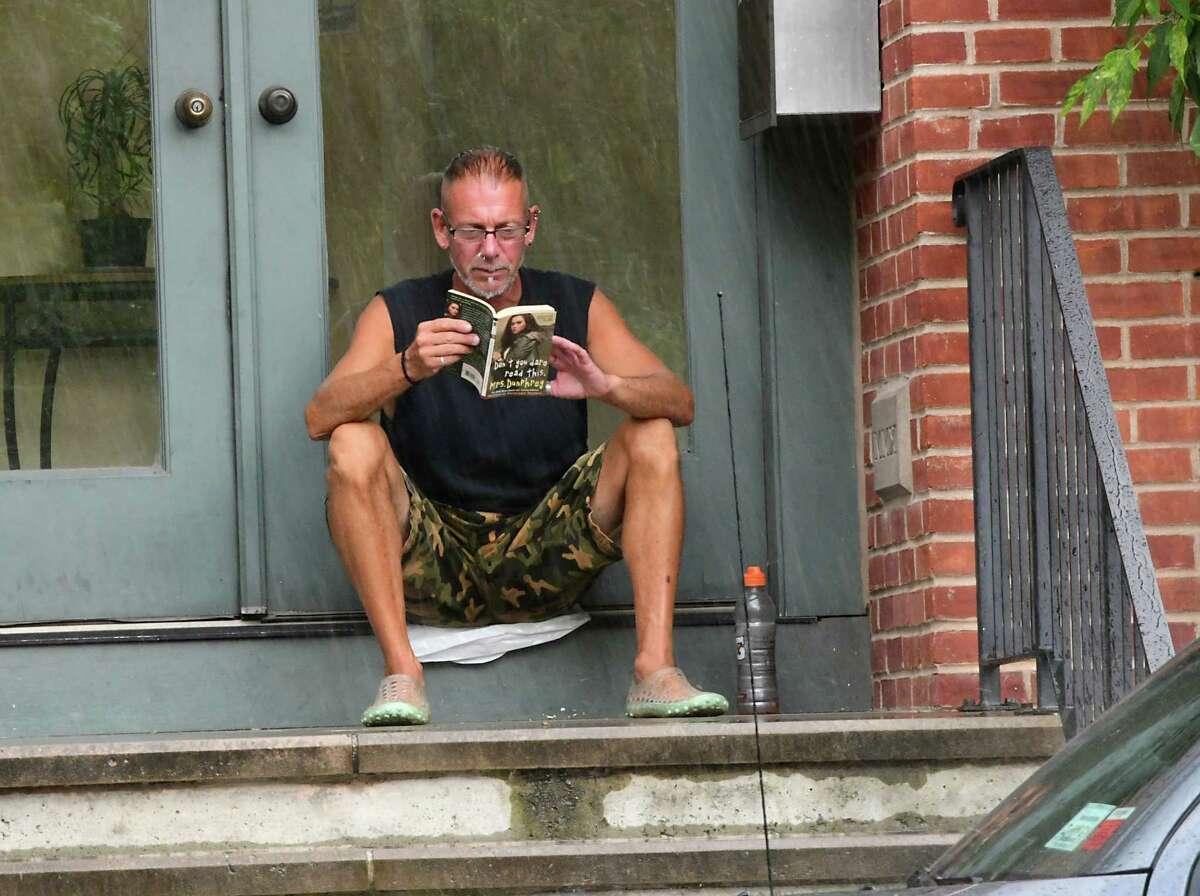Paul DeMarco finds a dry spot near the door of his apartment building to read a book on Madison Ave. during a downpour on Thursday, Aug. 8, 2019 in Albany, N.Y. (Lori Van Buren/Times Union)
