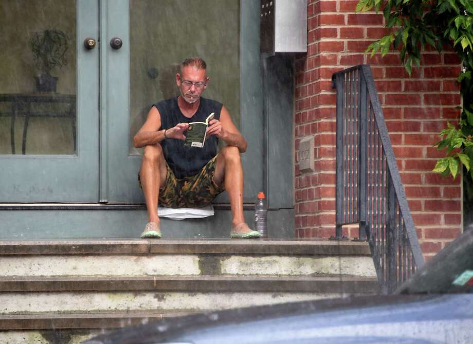 Paul DeMarco finds a dry spot near the door of his apartment building to read a book on Madison Ave. during a downpour on Thursday, Aug. 8, 2019 in Albany, N.Y. (Lori Van Buren/Times Union) Photo: Lori Van Buren, Albany Times Union