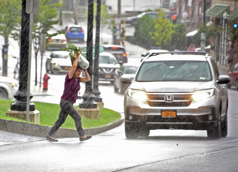 A woman covers her head with her grocery bag as she crosses New Scotland Ave. during a downpour on Thursday, Aug. 8, 2019 in Albany, N.Y. (Lori Van Buren/Times Union) Photo: Lori Van Buren, Albany Times Union