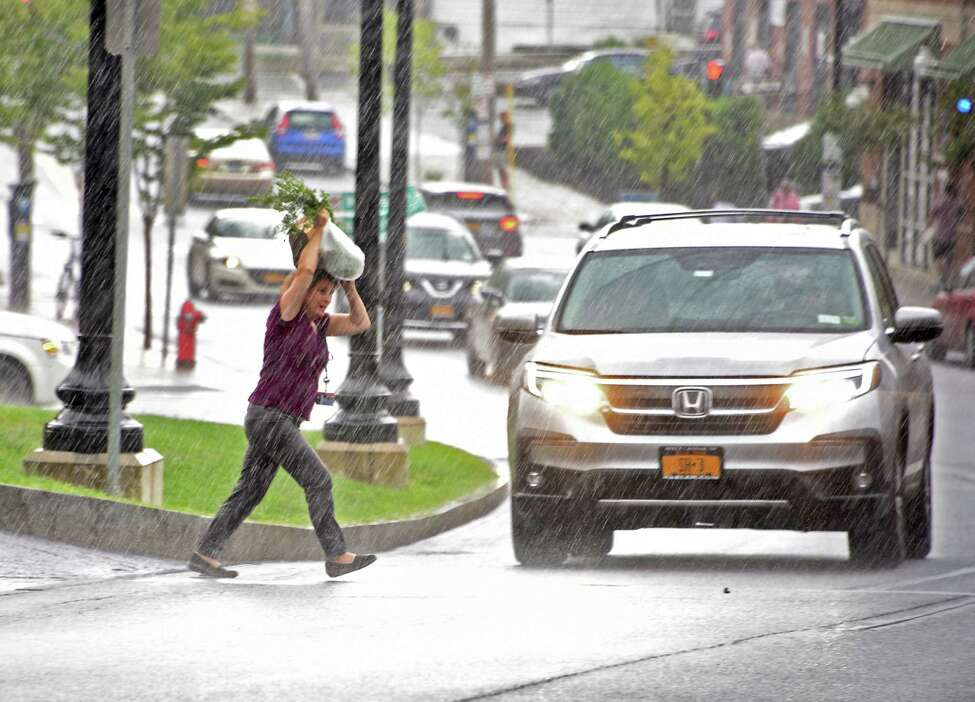 A woman covers her head with her grocery bag as she crosses New Scotland Ave. during a downpour on Thursday, Aug. 8, 2019 in Albany, N.Y. (Lori Van Buren/Times Union)