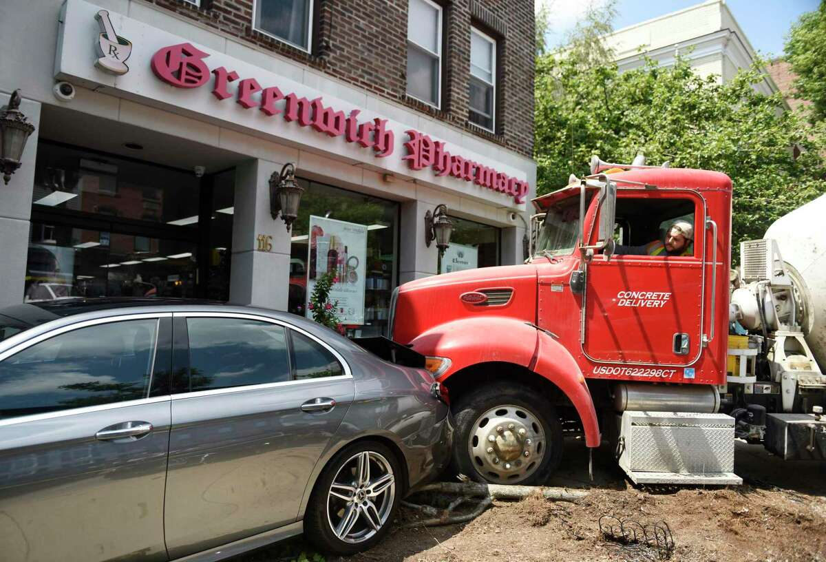 A cement mixer is removed from the scene in which it ran into a parked car outside Greenwich Pharmacy on Greenwich Avenue in Greenwich, Conn. Thursday, Aug. 8, 2019. The cement mixer plowed into the back of the parked car, pushing it onto the sidewalk and taking out a small tree in the process. The owner of the car was dining nearby at MIKU Sushi at the time of the accident, which attracted quite a bit of attention from passersby.