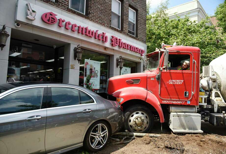 A cement mixer is removed from the scene in which it ran into a parked car outside Greenwich Pharmacy on Greenwich Avenue in Greenwich, Conn. Thursday, Aug. 8, 2019. The cement mixer plowed into the back of the parked car, pushing it onto the sidewalk and taking out a small tree in the process. The owner of the car was dining nearby at MIKU Sushi at the time of the accident, which attracted quite a bit of attention from passersby. Photo: Tyler Sizemore / Hearst Connecticut Media / Greenwich Time