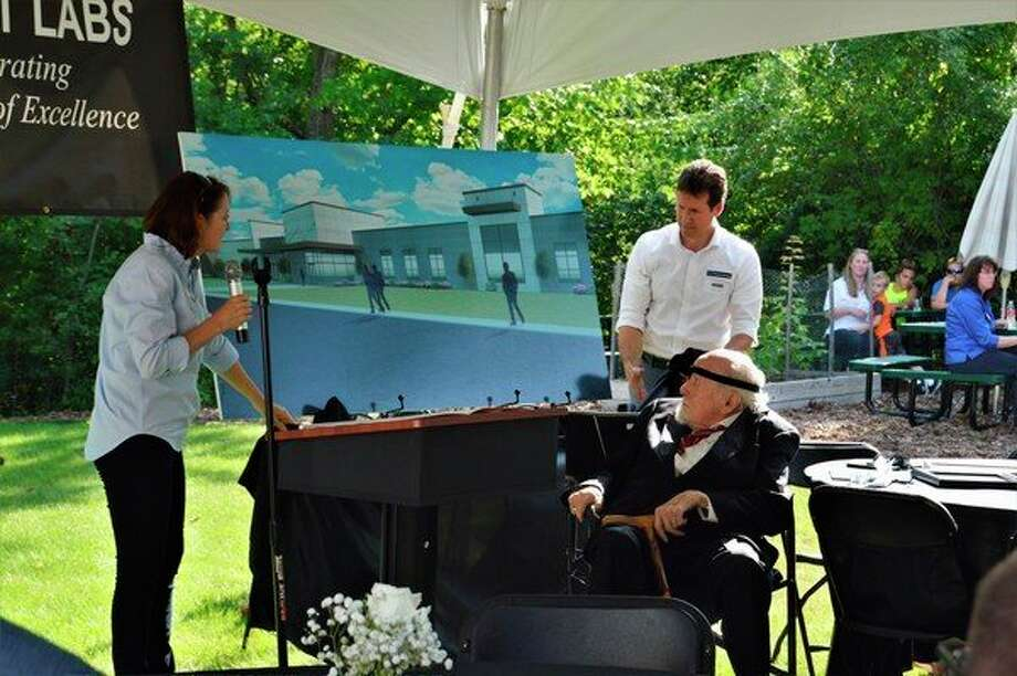 President of Savant group Rebecca Cox (left) and her husband, Vice President of Marketing and Sales, Gordon Cox (right), unveil the concept drawing for the new headquarters building with Founder Ted Selby (middle) at the 50th anniversary event on Wednesday, Aug. 7, 2019. (Ashley Schafer/ashley.schafer@hearstnp.com)