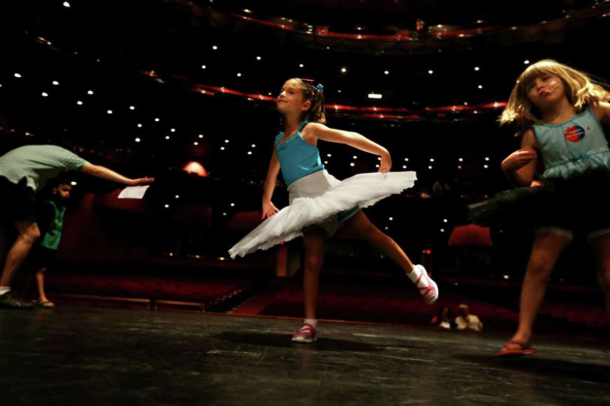 Ballerinas for a day, Glory Kanatzar-Fuller, center, and Piper Ferraz, both of Houston, on stage in the Brown Theater at the Wortham Theater Center during the 22nd Annual TransCanada Theater District Open House Sunday in 2015.