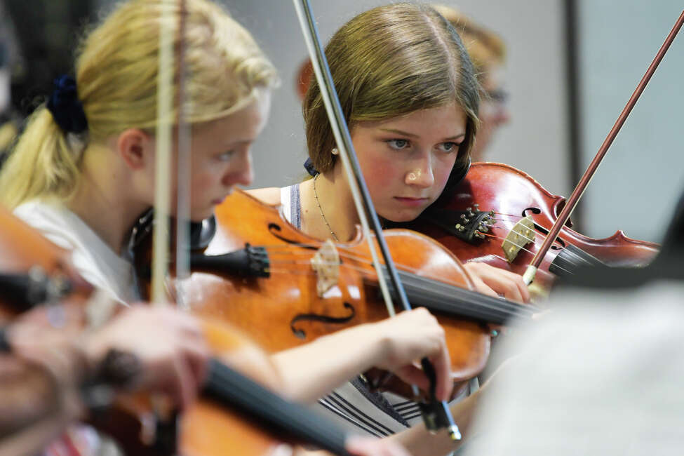Gracie Reppenhagen, 13, a member of the Queensbury High School Chamber Orchestra, takes part in the third annual