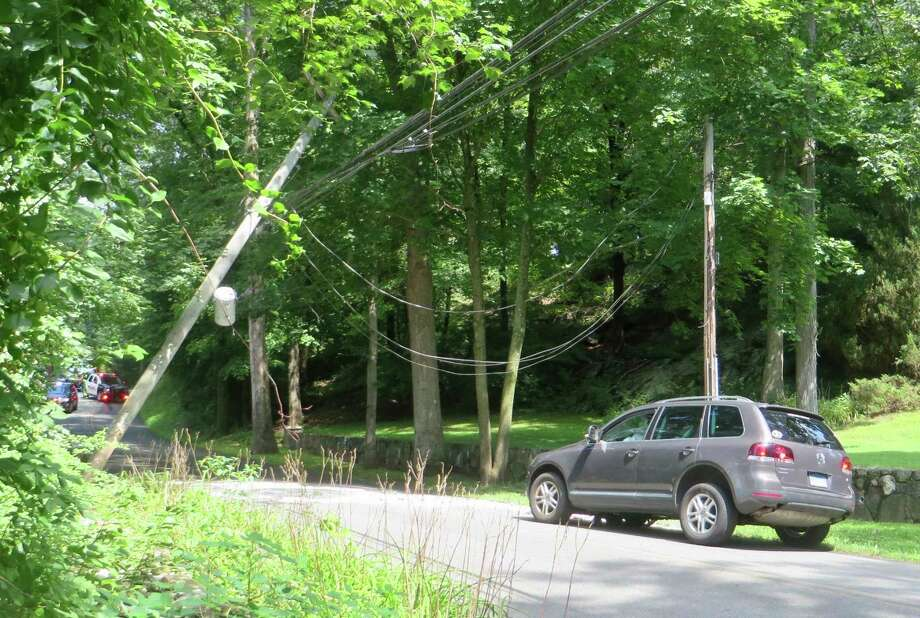 Wires hold a pole aloft after it was struck by an SUV on Marvin Ridge Road in New Canaan Thursday, Aug. 8. Photo: Contributed Photo / Peter Hanson / New Canaan Advertiser Contributed