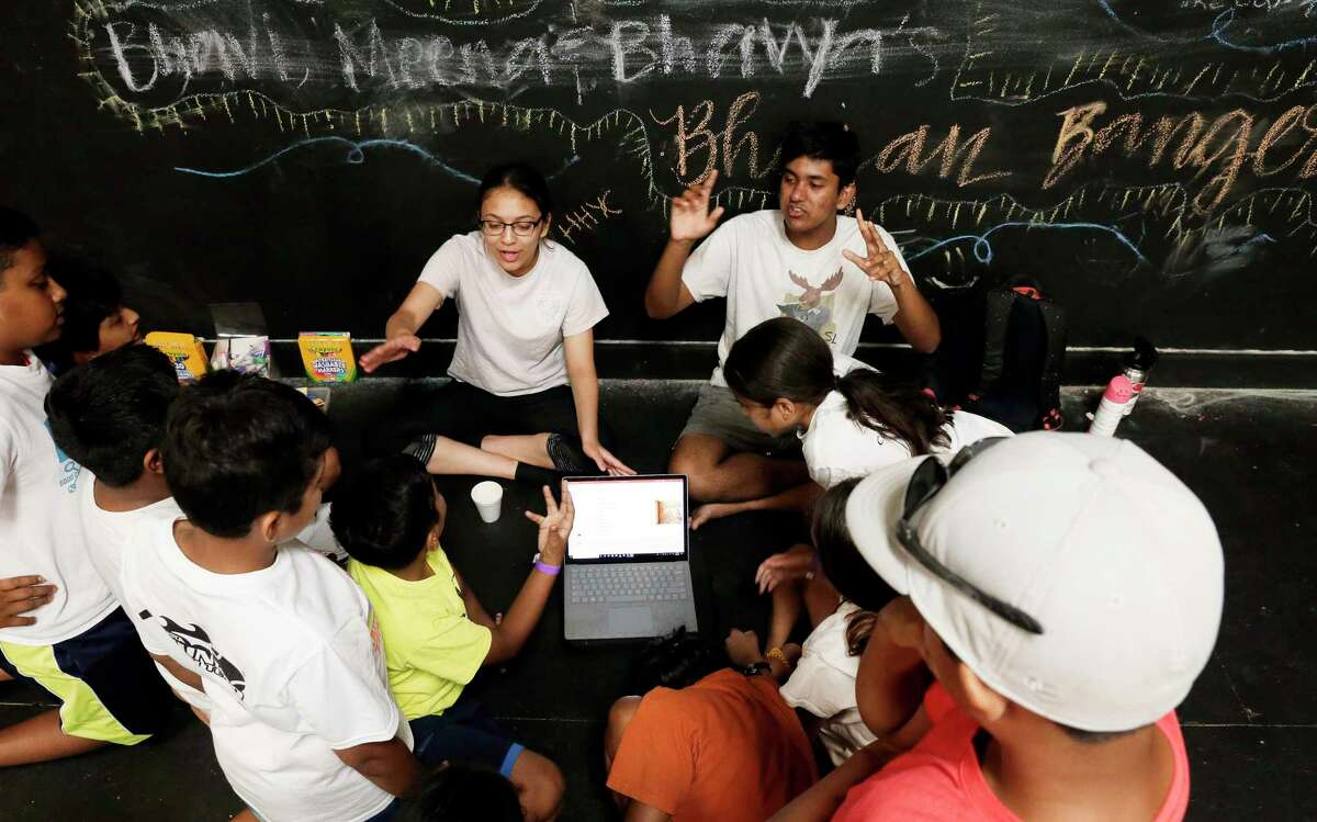 Camp counselors lead a class on Hindu traditions and history with elementary and middle school aged kids at the back of a stage with chalk writings on the wall behind them at the Hindu Heritage Youth Camp at Camp Lantern Creek near Montgomery.