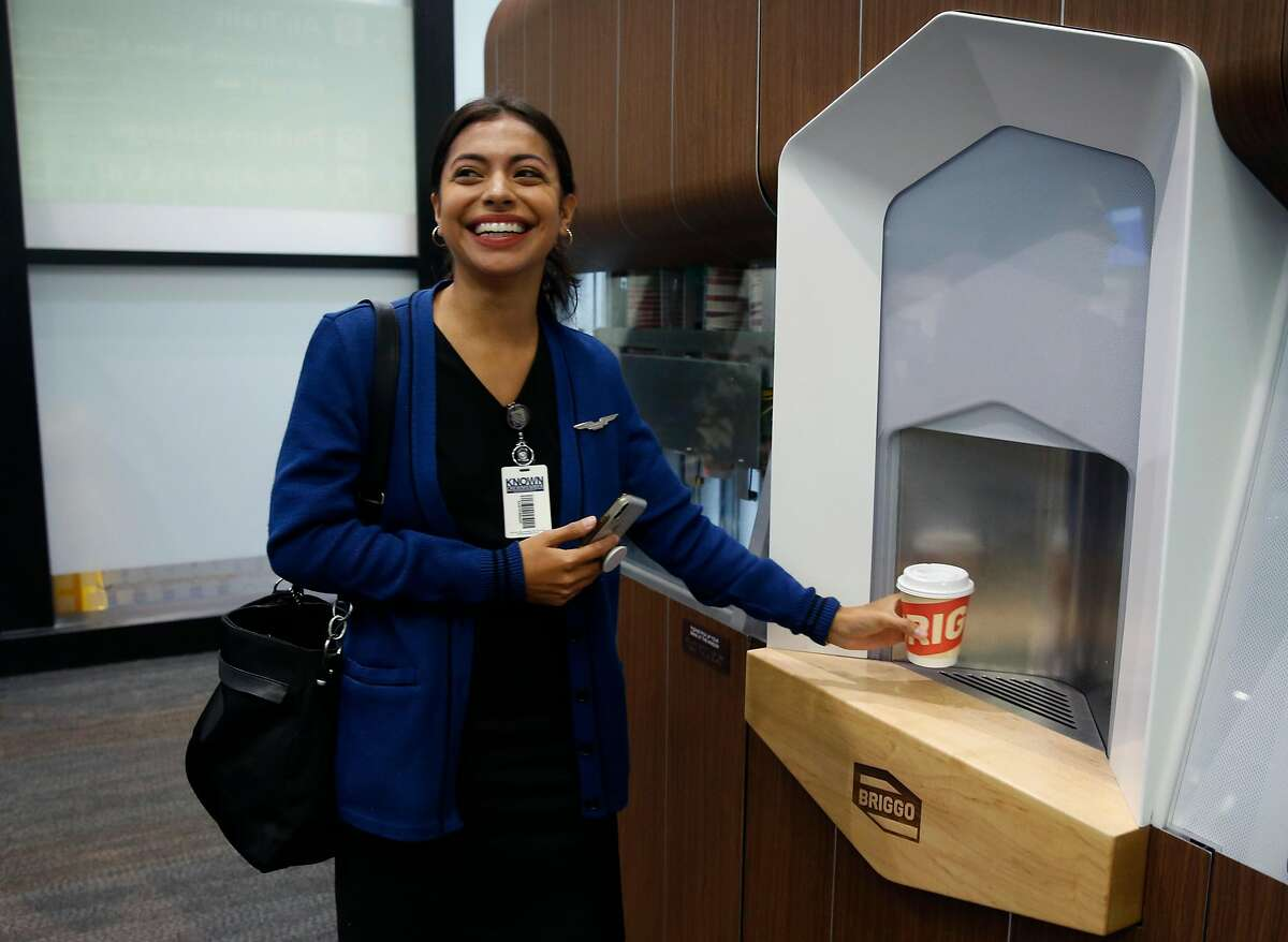 Flight attendant Brenda Chavez picks up her cup of coffee made by a robotic barista in Terminal 3 at SFO before she serves coffee to passengers aboard a flight to Los Angeles in San Francisco, Calif. on Thursday, Aug. 8, 2019. The automated Briggo Coffee Haus kiosk has been popular with both airport employees and travelers since it opened for business one week ago.