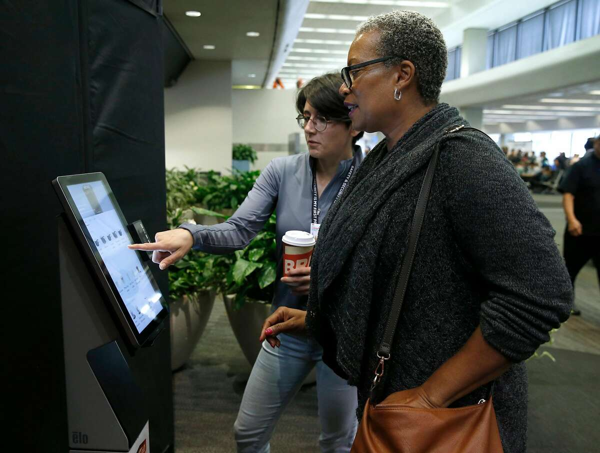 Danielle Pedersen helps Evelyn Beck (right) place an order from a robotic barista making caffeinated beverages in Terminal 3 at SFO in San Francisco, Calif. on Thursday, Aug. 8, 2019. The automated Briggo Coffee Haus kiosk has been popular with both airport employees and travelers since it opened for business one week ago.
