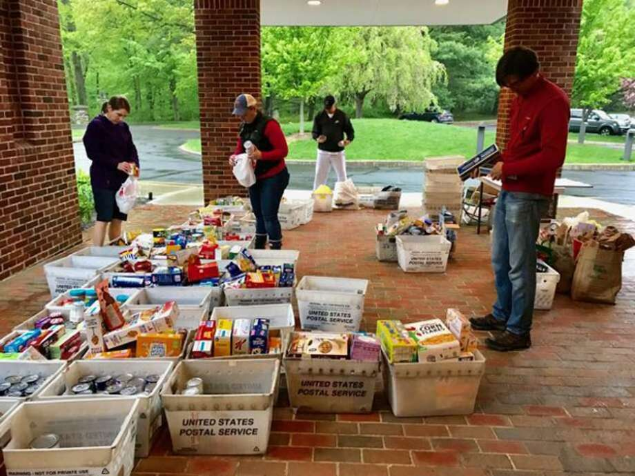 The New Canaan Food Pantry at St. Mark's Episcopal Church, which is located at 111 Oenoke Ridge in New Canaan, Connecticut, being stocked, and also organized by people preparing the items from it for delivery to places in the community. Photo: Contributed Photo