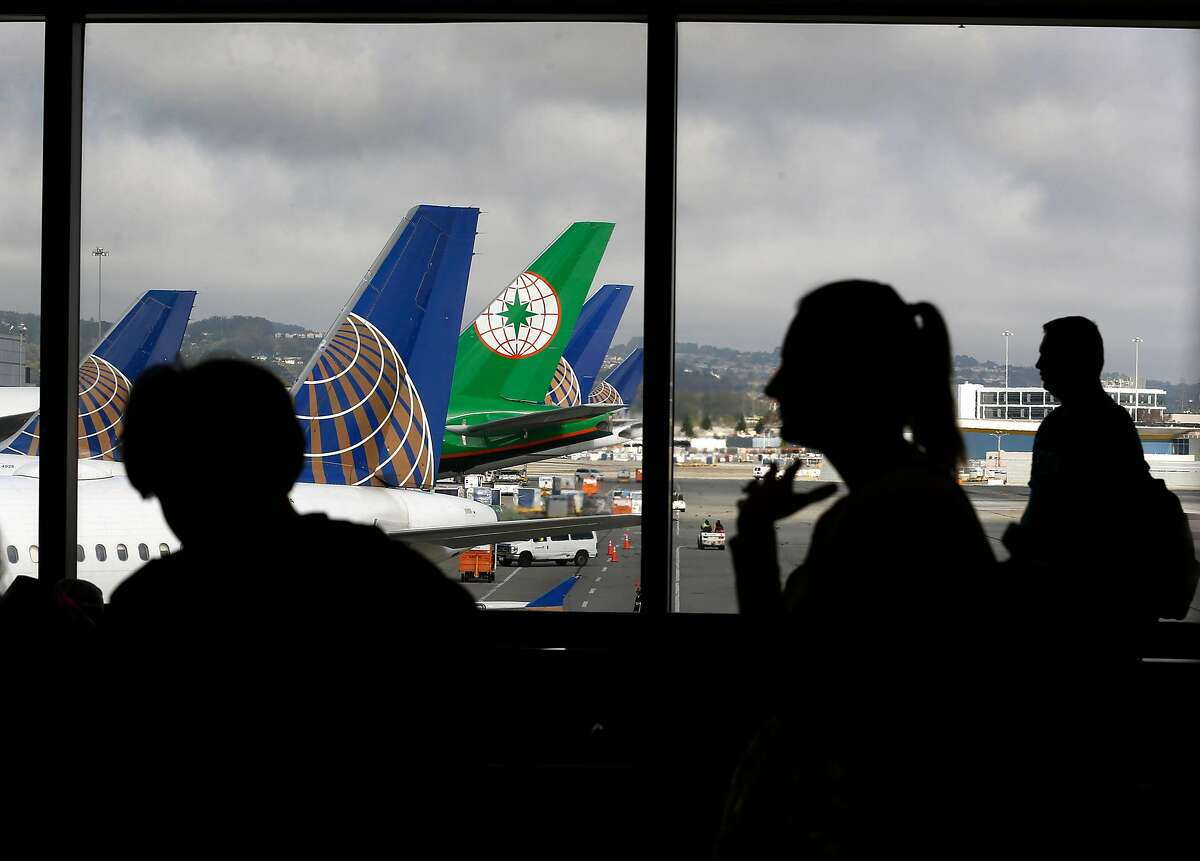 """Passengers wait to board a flight in Terminal 3 before Rep. Mark DeSaulnier and retired airline Capt. Chesley """"Sully"""" Sullenberger announce the Safe Landings Act legislation, inspired by the recent near-miss at SFO, during a news conference on Aug. 8, 2019."""